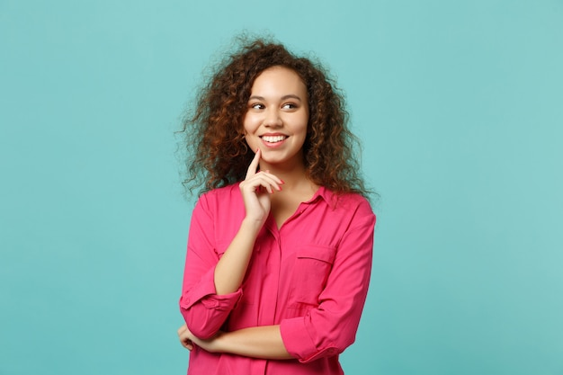 Une drôle de fille afro-américaine en vêtements décontractés a mis la main sur le menton, regardant de côté isolée sur fond bleu turquoise en studio. les gens émotions sincères, concept de style de vie. maquette de l'espace de copie.