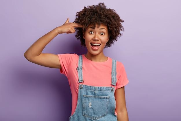 Drôle fille afro positive fait un geste de pistolet, tire dans le temple, montre un signe de suicide