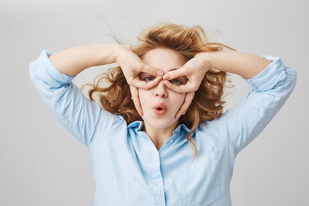 Drôle de fille aux cheveux bouclés ludique faisant masque de mains imitant le super-héros