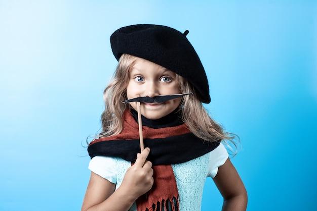 Drôle fille en béret noir, écharpe et moustache sur un bâton bleu
