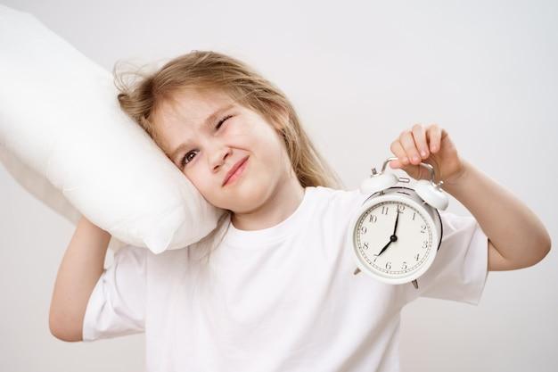Une drôle de fille endormie embrasse un oreiller et un réveil sur fond blanc. les premières ascensions des enfants à l'école et à la maternelle. literie confortable.