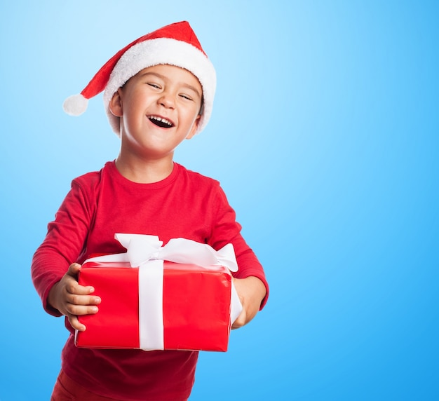 Drôle garçon tenant un cadeau rouge sur fond bleu