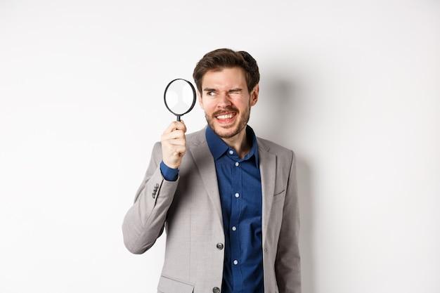 Drôle de gars en costume enquêtant ou recherchant quelque chose, regardant à travers une loupe, debout sur fond blanc.