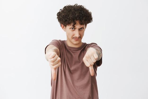 Drôle de gars juif mécontent et peu impressionné avec des cheveux bouclés et une moustache regardant sous le front avec un regard fou montrant les pouces vers le bas dans un geste de dégoût donnant des commentaires négatifs ou une réponse