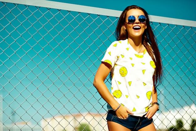 Drôle glamour fou élégant sexy souriant belle jeune femme modèle dans des vêtements décontractés d'été hipster lumineux dans la rue derrière le ciel bleu
