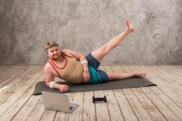 Drôle gros homme en vêtements de sport, faire des exercices. il fait du sport à distance tout en regardant son ordinateur portable.