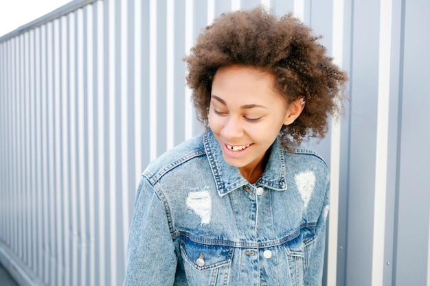 Drôle heureuse femme afro noire en t-shirt blanc et jeans