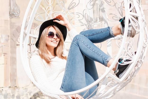 Drôle heureux jeune femme hipster en blue-jeans dans un pull tricoté dans un chapeau à la mode en lunettes de soleil rondes sur une journée ensoleillée d'été. fille heureuse reposant sur une chaise vintage suspendue blanche.