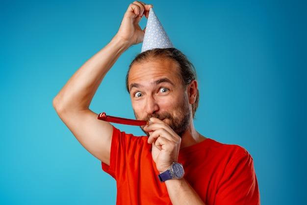 Drôle homme barbu aux cheveux longs en cône de fête contre le bleu