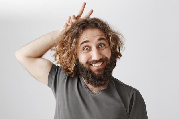 Drôle d'homme barbu du moyen-orient souriant et montrant des cornes au-dessus de la tête