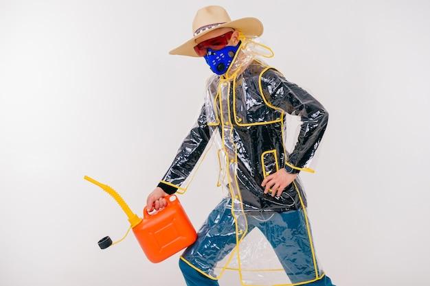 Drôle homme étrange élégant dans le masque et chapeau de paille avec arrosoir posant sur mur blanc