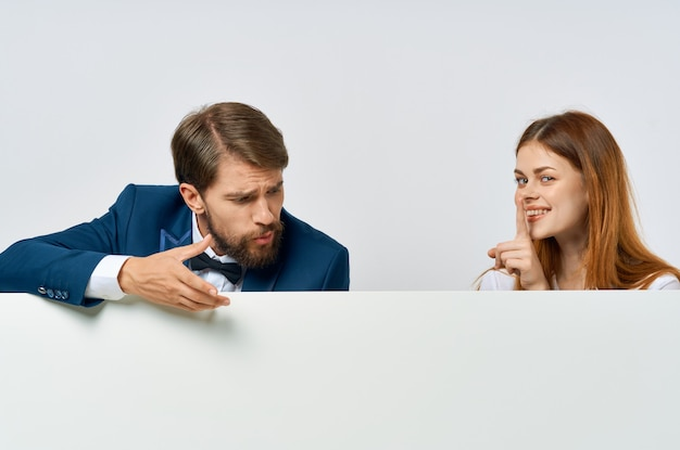 Drôle homme et femme tenant une affiche promotionnelle