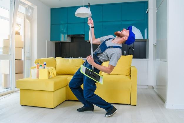 Drôle homme de ménage dans des vêtements bleus spéciaux jouant avec une vadrouille comme une guitare comme une rockstar dans la cuisine élégante. s'amuser au travail.