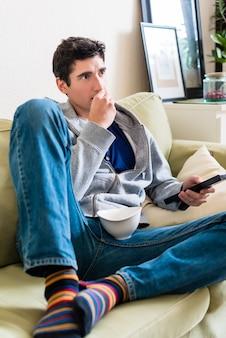Drôle jeune couple portant des vêtements décontractés tout en jouant ensemble un jeu vidéo sur console à la maison