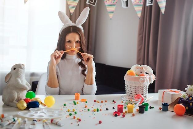 Drôle jeune femme bouleversée se prépare pour pâques seul. elle est assise à table dans la chambre et tient les pinceaux croisés. regarder le modèle sur la caméra. décoration avec peinture et bonbons sur table.