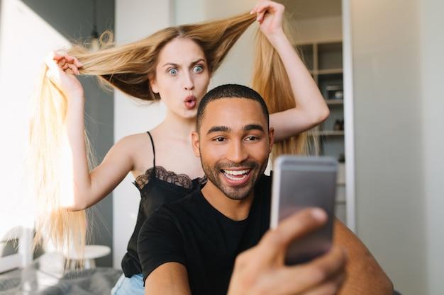 Drôle jeune femme excitée s'amusant avec ses longs cheveux blonds derrière un beau mec sourit faisant selfie d'eux sur le lit dans un appartement moderne. amoureux, bonheur, divertissement