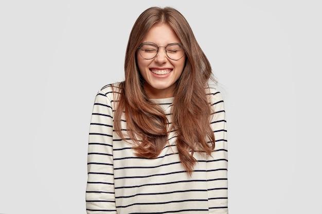 Drôle jeune femme avec des lunettes posant contre le mur blanc