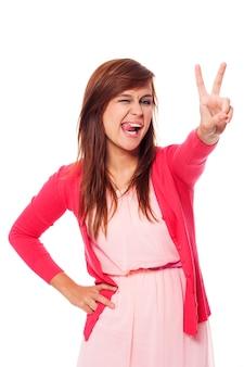 Drôle jeune femme montrant le signe de la victoire
