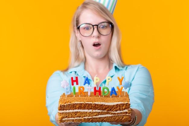 Drôle jeune femme positive tient dans ses mains un gâteau fait maison