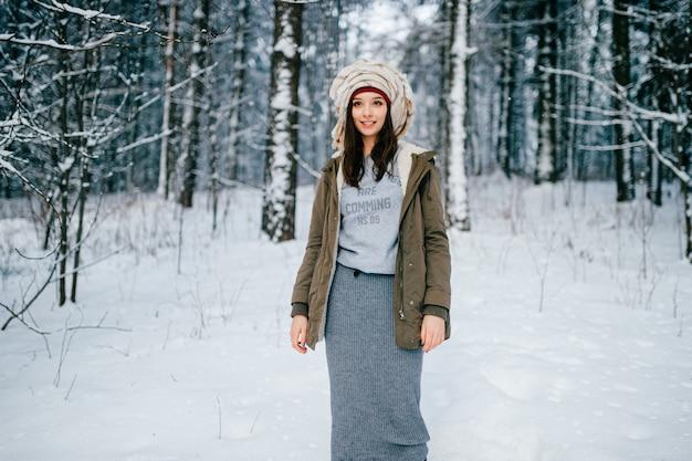 Drôle jeune fille brune séduisante avec un turban de l'écharpe posant dans la forêt de neige