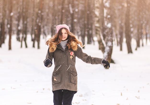 Drôle de jeune fille dans le parc en hiver traverse la neige