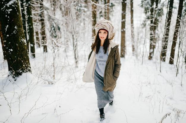 Drôle jeune fille séduisante avec un turban de l'écharpe marchant dans la forêt de neige