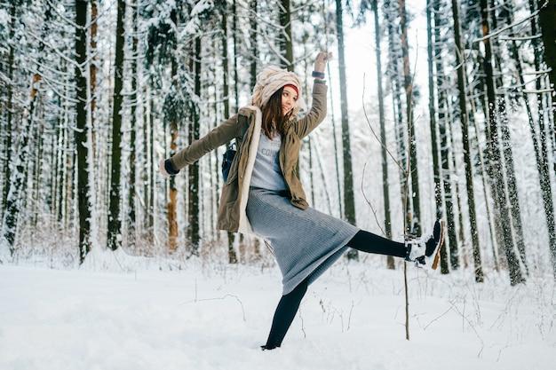 Drôle jeune fille séduisante avec un turban de l'écharpe posant dans la forêt de neige