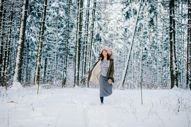 Drôle jeune fille séduisante avec un turban de l'écharpe qui court parmi les arbres dans la forêt de neige