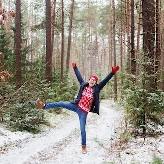 Drôle jeune homme au chapeau rouge dans la forêt d'hiver