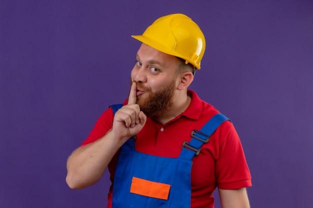 Drôle jeune homme constructeur barbu en uniforme de construction et casque de sécurité faisant le geste de silence avec le doigt sur les lèvres sur fond violet