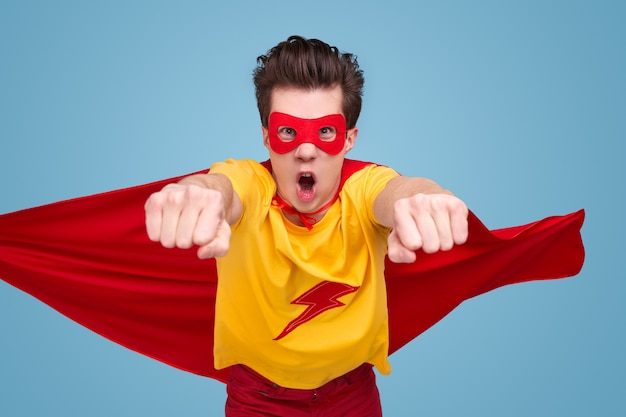 Drôle de jeune homme en costume de super-héros rugissant et volant vers la caméra tout en sauvant le monde sur fond bleu