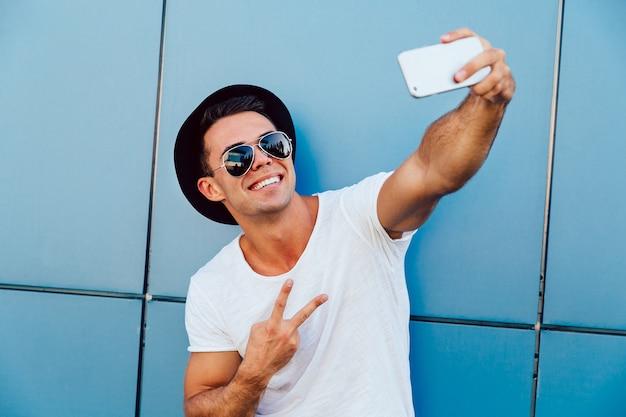 Drôle jeune homme à lunettes de soleil et chapeau noir prend un selfie, montrant un signe de paix