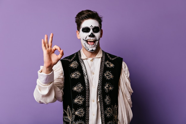 Drôle jeune homme montre signe ok. portrait intérieur de gars avec visage peint pour halloween.