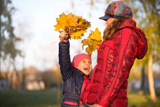 Drôle jeune mère et une jolie petite femme avec un bouquet