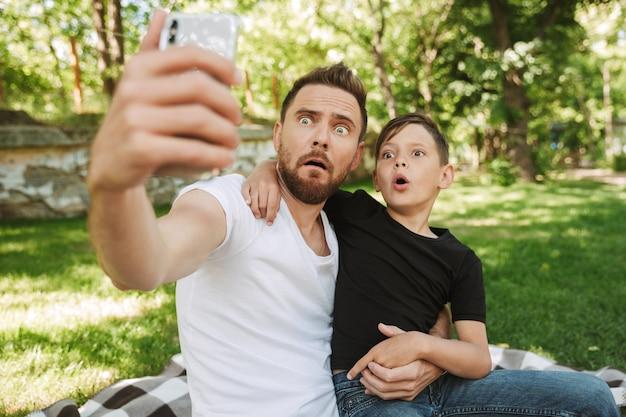 Drôle jeune père assis avec son petit fils fait selfie par téléphone mobile.