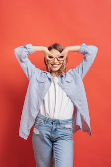 Drôle, jolie fille s'amuser isolée sur un mur rouge tout en faisant des jumelles mains.