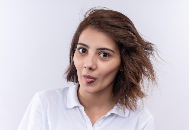 Drôle joyeuse jeune fille aux cheveux courts portant un polo blanc regardant la caméra qui sort la langue