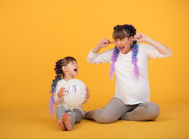 Drôle de mère enceinte et de petite fille dans les mêmes vêtements et coiffures tiennent une balle dans leurs mains et attendent qu'elle éclate. concept d'attendre un nouveau bébé dans la famille. copyspace