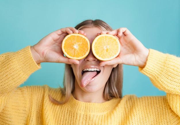 Drôle de modèle couvrant les yeux avec des oranges
