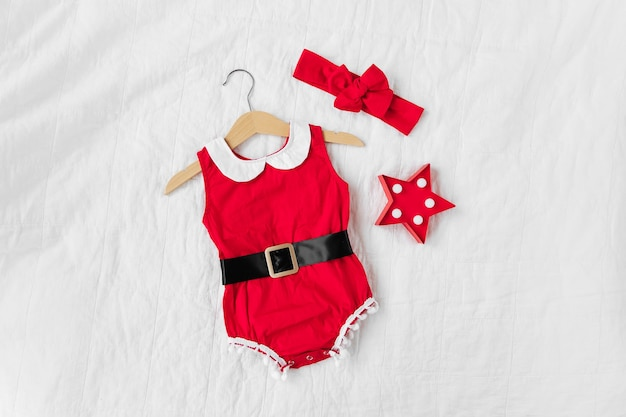 Drôle de petit déguisement de père noël pour petite fille sur le lit. joyeux noël.