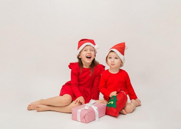 Drôle de petit garçon et fille en bonnets rouges avec des cadeaux de noël sur un mur blanc avec un espace pour
