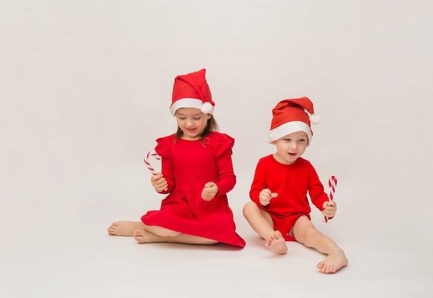 Drôle de petit garçon et fille en bonnets rouges avec des sucettes sur un mur blanc