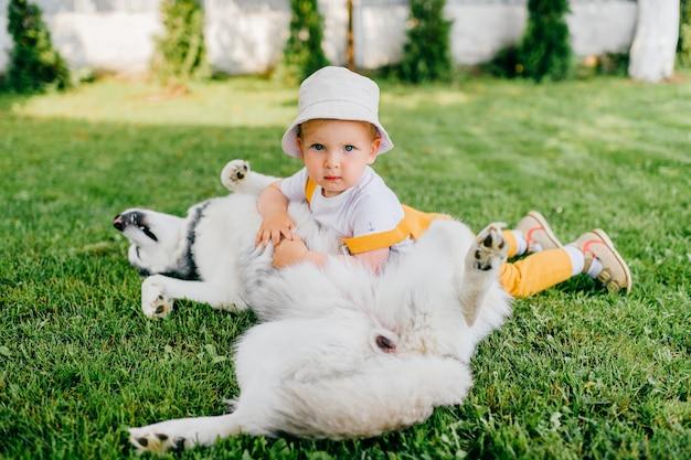 Un drôle de petit garçon posant avec le chien dans le jardin
