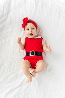Drôle de petit père noël. jolie petite fille dans un costume de père noël rouge sur le lit. joyeux noël.