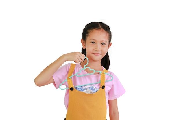 Drôle de petite fille asiatique tenant un cintre en plastique avec son vêtement isolé sur fond blanc. image avec chemin de détourage