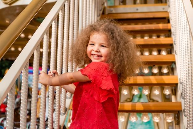 Drôle de petite fille bouclée dans une robe rouge dans les escaliers avec des lampes de poche