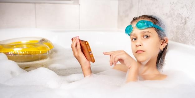 Drôle de petite fille caucasienne dans des lunettes de natation surfe sur internet à l'aide d'un smartphone