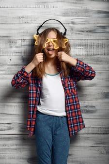Drôle de petite fille dans les écouteurs et les lunettes étoiles en studio. enfants et gadget, enfant isolé sur fond en bois, émotion de l'enfant, séance photo d'écolière