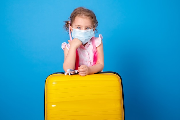 Drôle de petite fille dans un masque de protection avec avion jouet et valise jaune sur une surface bleue.