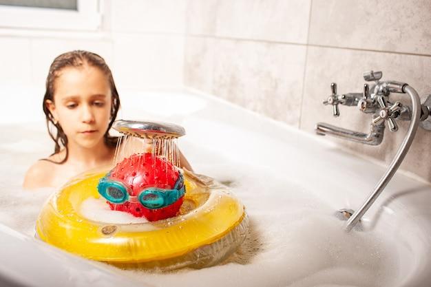Drôle de petite fille douche une tête faite d'une balle et de lunettes de natation